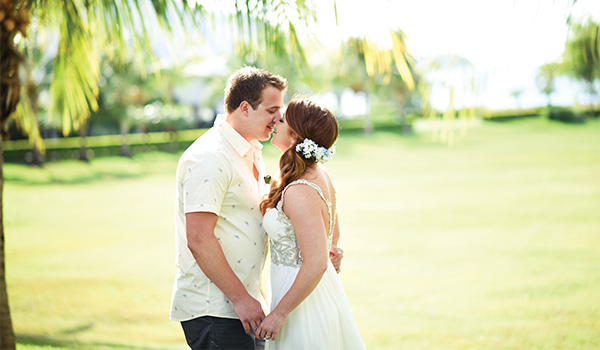 Bride and groom kissing in a lush garden