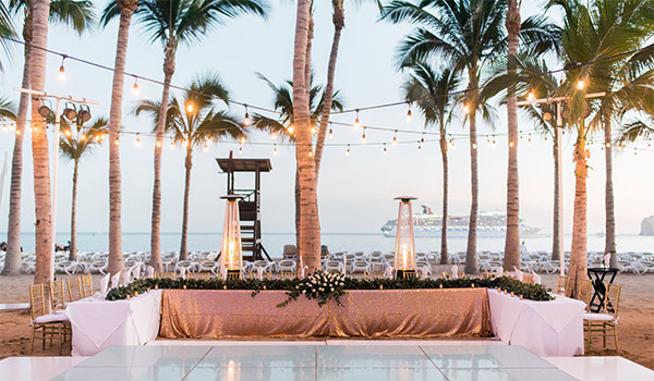 Wedding reception on the beach decorated in pink and white