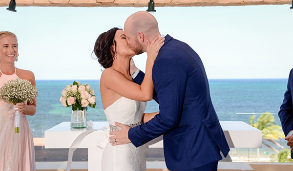 Bride and groom kissing on a terrace overlooking the ocean