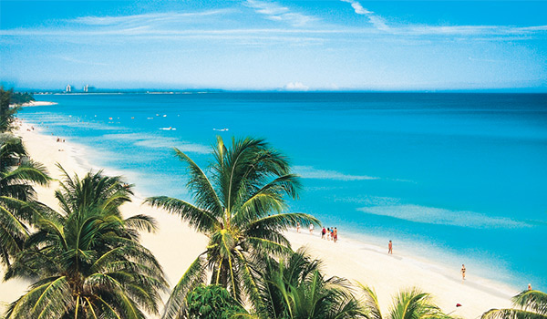 Aerial view of Varadero Beach with white-sand shores blending into bright blue waters and towering palm trees.