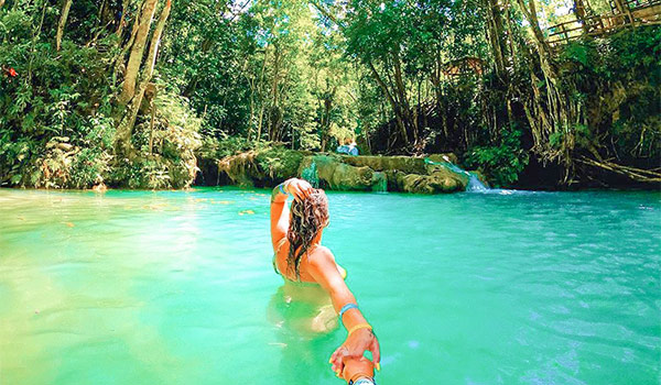 Woman swimming in a turquoise pool surrounded by the lush jungle