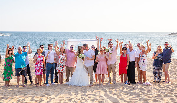 Group shot of the wedding party and guests on the beach