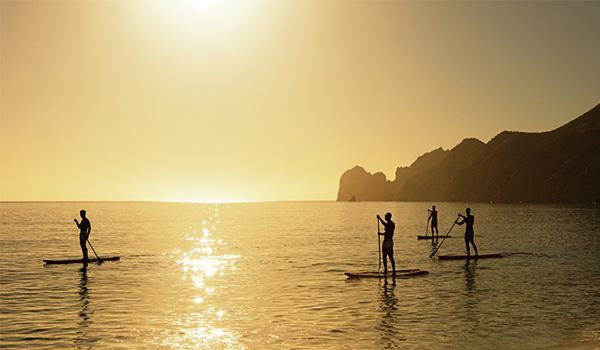 Plusieurs personnes utilisant des planches à pagaie le long de la plage au coucher du soleil.
