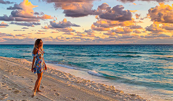 Woman in a dress standing on the beach at sunset