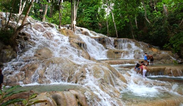 People climbing up the tiered cascades of Dunns River Falls