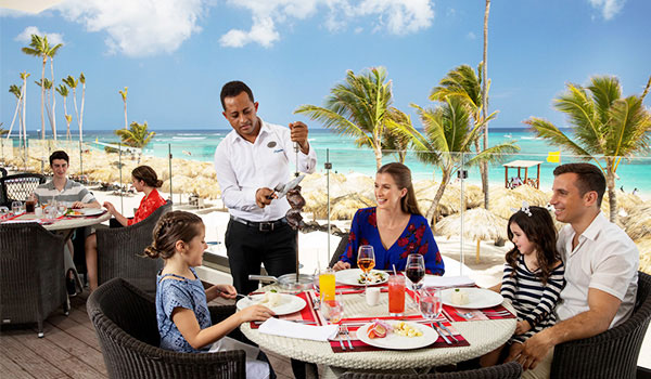 Family enjoying a meal an outdoor terrace overlooking the beach