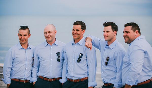 Groomsmen posing on the beach