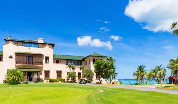 Parcours de golf de style colonial, avec l'océan à l'horizon