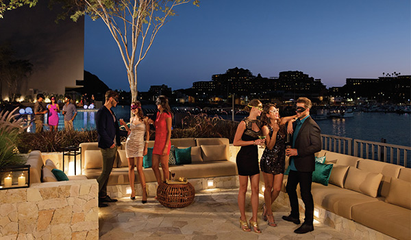 Party-goers wearing fancy outfits and masquerade masks mingling on an outdoor terrace