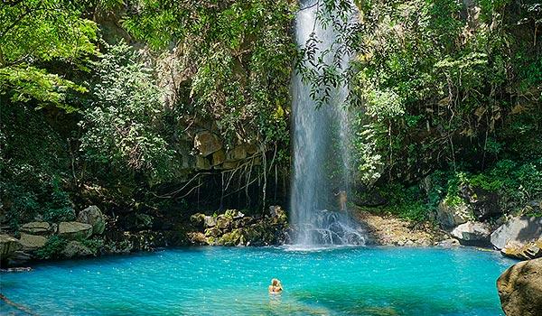 Femme nageant dans un bassin cristallin au pied d'une grande chute d'eau dans la forêt