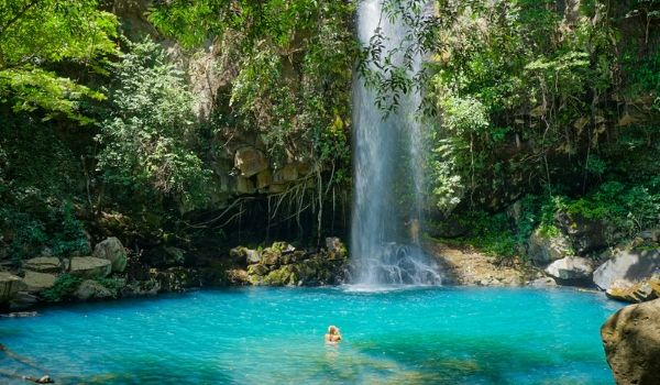 Woman swimming in the crystal-clear pool below a towering waterfall in the forest