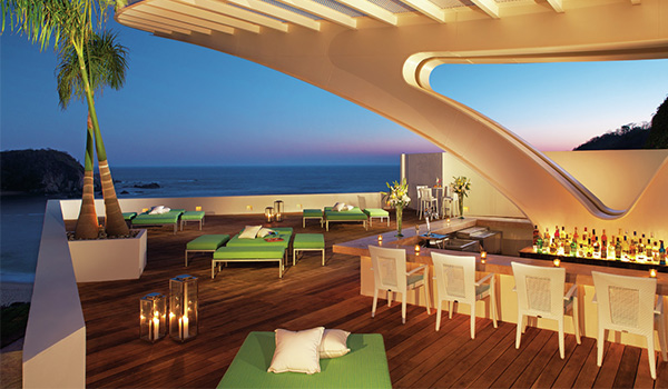 Rooftop bar overlooking the ocean at sunset