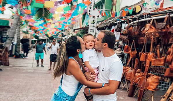 Man and woman kissing a baby on the cheek on a city street