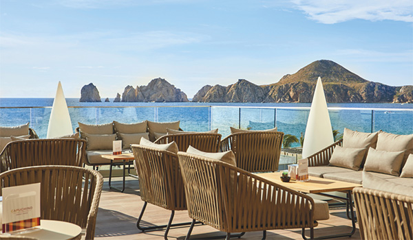 Patio with tables and chairs overlooking the rocky coast