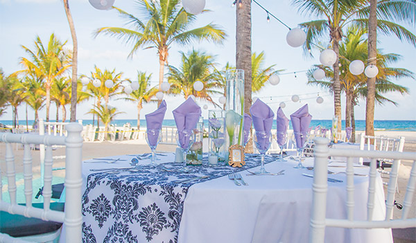 Wedding reception on the beach with purple decor