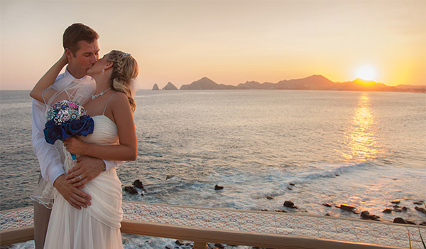 Groom and bride standing on the beach at sunset