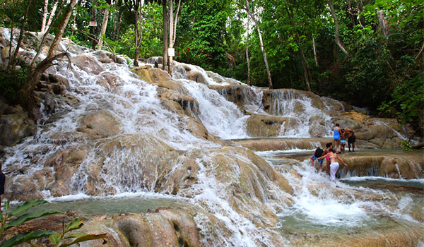 People climbing the rushing cascades of Dunn's River Falls
