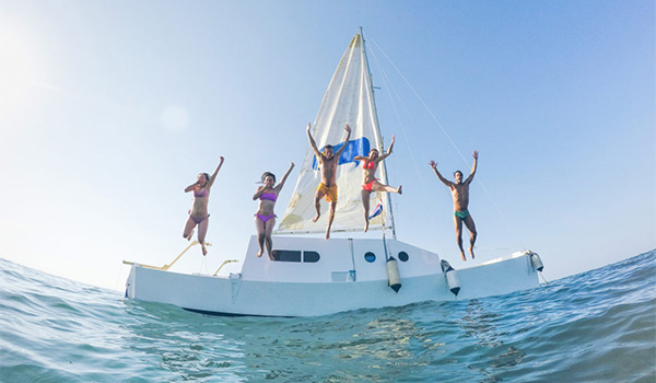 Group of friends jumping into the ocean off a catamaran