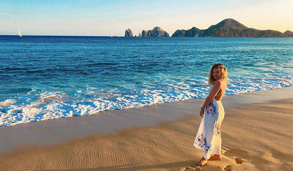 Woman standing on the beach with El Arco in the distance