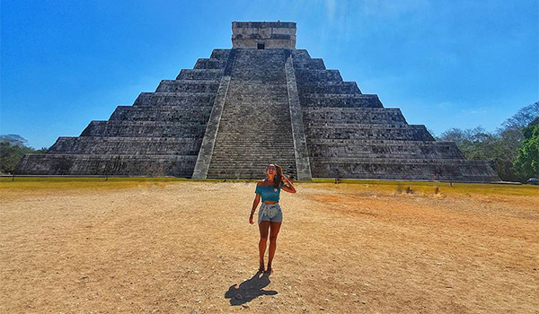 Woman standing in front of ancient Mayan ruins