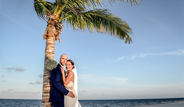 Bride and groom standing underneath a palm tree