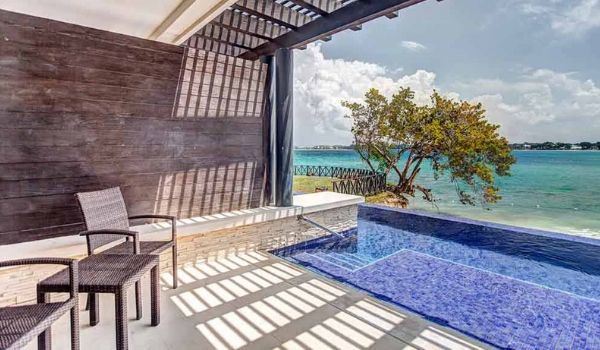 A private terrace with an infinity pool overlooking the ocean on a sunny day