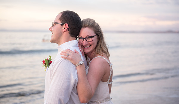 Groom and bride hugging on the beach at sunset