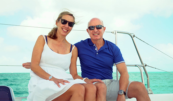 Dr. Nord and his wife sitting on the deck of a catamaran