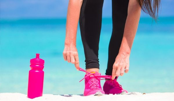 Woman lacing up sneakers on beach