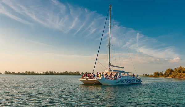 Catamaran cruising along the coast of Cayo Largo at sunset