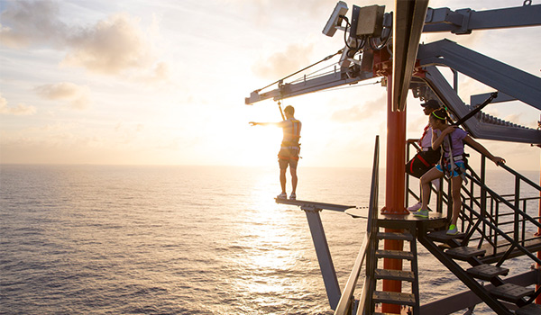 Person walking on a plank over the ocean from a cruise ship deck