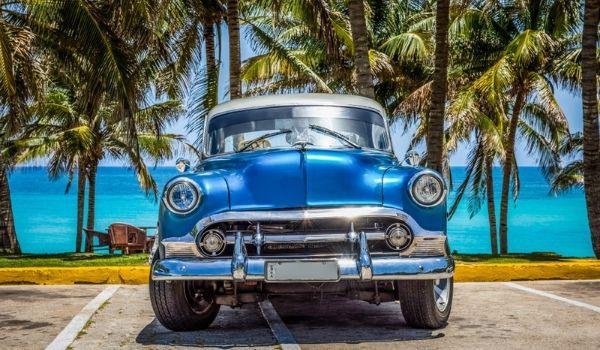 Voiture classique américaine bleue stationnée devant une plage menant à l'eau bleue