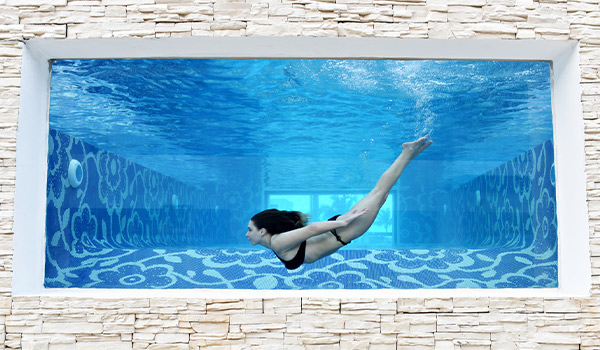 Un mur de verre à travers lequel on voit une femme qui nage dans la piscine Mermaid