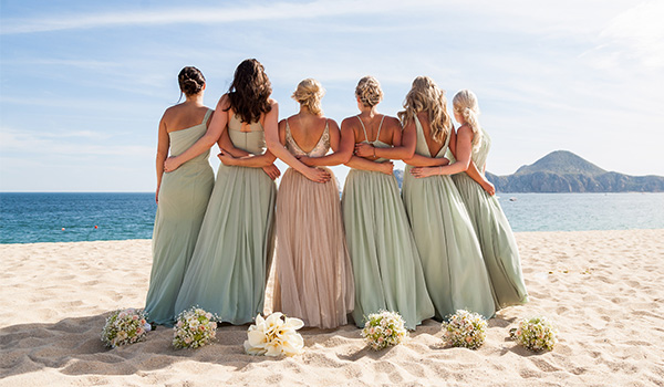 Bride and her bridesmaids posing on the beach