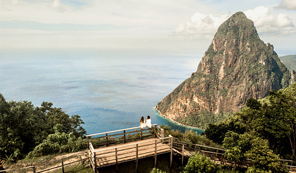 Two people sitting on a bridge overlooking the Piton Mountains