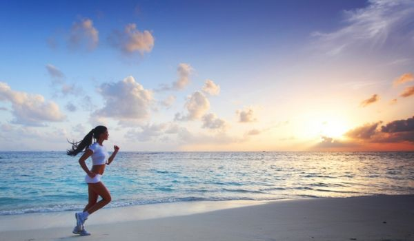Woman running down the beach at sunset