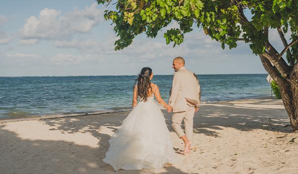 Groom and bride walking towards the beach
