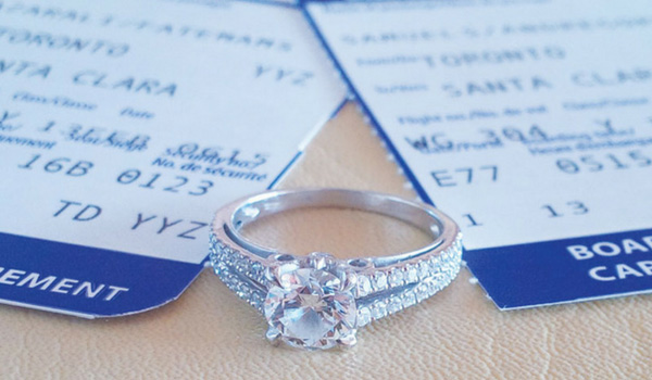 Engagement ring sitting on top of a boarding pass