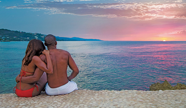 Man and woman sitting at edge of cliff looking at sunset