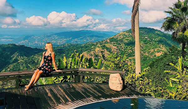 Woman sitting on a balcony overlooking tree-covered mountains