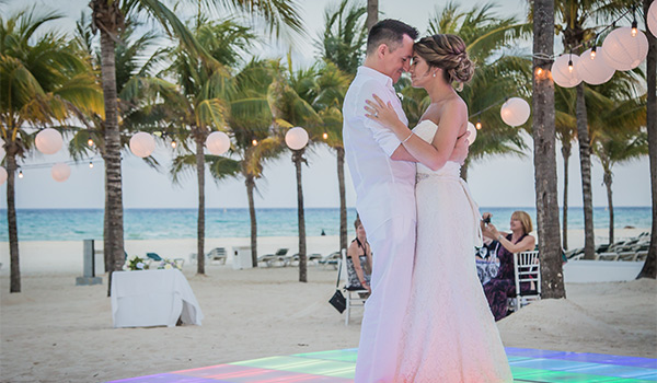 Bride and groom dancing on a multi-coloured dancefloor on the beach