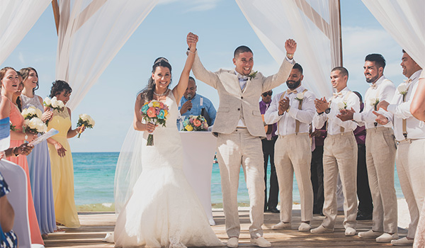 Ana and Emmanuel hold hands as they walk down the aisle