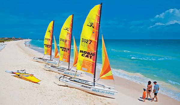 Homme, femme et garçon marchant devant des catamarans Hobie Cat sur la belle Playa La Estrella