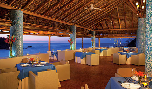 Elegant open-air restaurant with a thatched roof overlooking the sea at sunset