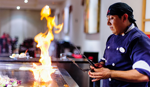 Chef cooking over a Teppanyaki stove