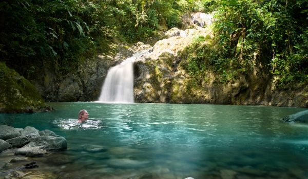 Woman swimming in the pool of a waterfall