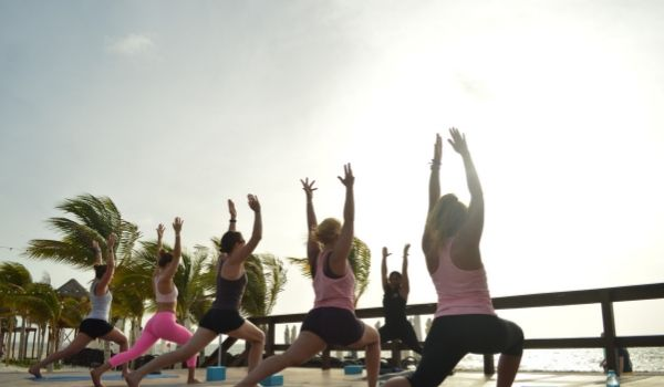 Group of people doing sunrise yoga by the beach
