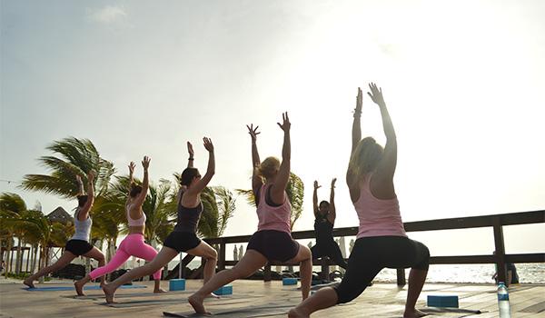 Groupe de personnes pratiquant le yoga à la plage au coucher de soleil