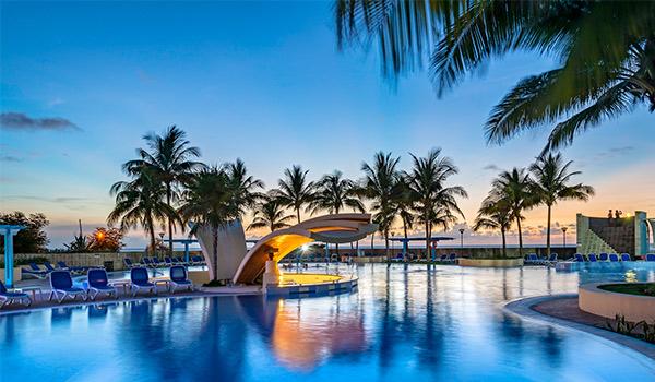 Aire de piscine éclairée au crépuscule avec des palmiers au loin