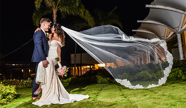 Bride and groom posing in a garden at night